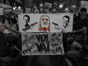 "Protests against World Cup in Rio: Protesters display a banner of Mayor Eduardo Paes and State Governor Sergio Cabral holding Rio de Janeiro's famous Christ statue hostage. The banner below reads ""Who gives the order? Who gets the progress?"""