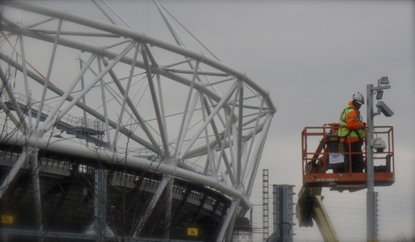 London Olympic stadium on the left: in the foreground on the right workers installing some of the 900 day and night vision cameras which top the 17.5 km, 5,000 volt electrified fence which surrounds the entire Olympic enclosure